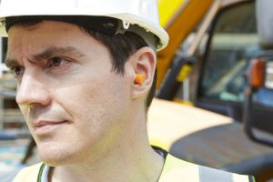 A construction worker wears earplugs.