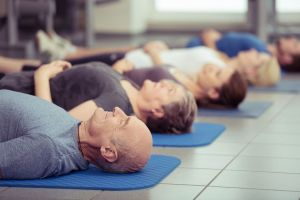 adults lying on floor of gym relaxing after fitness class